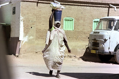 76-230 (ndpa / s. lundeen, archivist) Tags: nick dewolf color photograph by 1976 1970s film 35mm 76 reel76 early1976 africa northernafrica northeastafrica sudan thesudan african sudanese khartoum city town candid streetphotography streetlife citylife people building woman basket load balance balancing carry carrying onherhead headcovering truck vehicle street pedestrian tob hijab tobe khartoumstate photographbynickdewolf