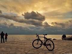 Cloudy afternoon (mary.th) Tags: afternoon clouds sky sea people bicycle sunset