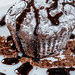 Chocolate muffin with powdered sugar poured chocolate topping