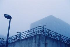 Monochrome Morning (not without my camera(s)) Tags: film filmlebt 35mm grain grainy fog foggy winter bluetone bluehour morning cold monochrome urban city bochum building bikes streetlamp streetscene concrete meinfilmlab wwwmeinfilmlabde canonae1 canonfilmphotography