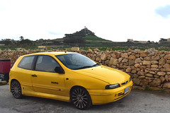 Yellow 2-door Momo edition (D70) Tags: zebbuj gozo malta yellow 2door momo edition stone fench sculpture buildings cross