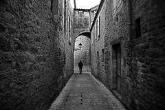(cherco) Tags: man vanishingpoint city composition composicion canon ciudad calle solitario solitary silhouette silueta sombra street shadows alone architecture arquitectura aloner arch arco adoquinado lonely loner sombras france blackandwhite blancoynegro markiii monochrome window village medieval lampara lamp