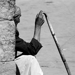 Old Man Sitting Against A Wall And Holding A Cane In Shibam, Yemen (Eric Lafforgue) Tags: adult alone amran arabia arabiafelix arabianpeninsula blackandwhite blue bluesky brick day man oldman oneperson placeofinterest realpeople rest sit square stick street unrecognizableperson wall wisdom yemen yemeni mg6097 shibam hadhramaut