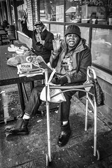 Selling Papers (tim.perdue) Tags: north market columbus ohio downtown urban city short arena district candid street black white bw monochrome nikon d5600 nikkor 18140mm men people figures speech newspaper salesman homeless sidewalk picnic table two duo walker