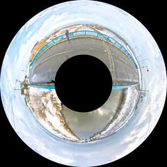 Around Naganuma with Swans, variant (sjrankin) Tags: 16march2019 edited naomi family panorama 360° 360°degrees 360°panorama animal birds swans water drainagecanal canal farms fields snow sky hills bridge naganuma hokkaido japan