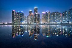 Busan Puddles (Scintt) Tags: bay water sky dramatic travel tourist attraction exploration movement motion skyline cityscape city urban modern structures architecture buildings offices scintillation scintt jonchiangphotography iconic surreal epic wideangle still calm glow light tones pond pool dusk twilight waterfront puddle symmetrical mirror reflection lensflare lowangle financial centre marina korea busan evening blue hour skyscrapers tall towers sony a7rii slowshutter longexposure night