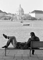 Relaxing (saxild) Tags: nikon f75 slr nikkor 85mm 85mm18d ilford fp4 analog film black white bw plustek opticfilm scanner 7400 street streetphotography streetphoto operaen amalienborg copenhagen cph denmark waterfront couple relaxing bench