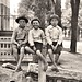 Three unidentified barefoot boys sitting on a hitching rail, location unidentified, undated (ca. 1890-1900).