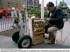 """Knife Grinder 1 (hoffman) Tags: abrasion abrasive bell cart grinder grinding handbell horizontal itinerant machine outdoors poor poverty repairing restoring saw selfemployed selfemployment sharpener sharpening sign sitting street trolley underpaid work working davidhoffman wwwhoffmanphotoscom london uk davidhoffmanphotolibrary socialissues reportage stockphotos""""stock photostock photography"""" stockphotographs""""documentarywwwhoffmanphotoscom copyright"""