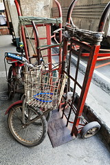 Handcarts and bicycles on the sidewalk under the arcade-Binondo Chinatown-Manila-Philippines-0992 (rweisswald) Tags: courierservice drivetrain crank chainring saddle spoke rim mudguard sidewalk pavement arcade quintinparedesroad binondodistrict chinatown manila philippines