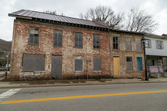 Abandoned Building — Ripley, Ohio (Pythaglio) Tags: building structure ripley ohio unitedstatesofamerica us historic twostory abandoned vacant browncounty 22windows boarded dilapidated stone lintels sills sevenbay sidewalk street trees steppedgable
