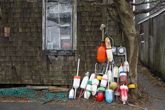Buoy Collection (brucetopher) Tags: lobster pot trap buoy rope twine gear colorful color colors primary winter storage coast coastal newengland waterfront seacoast town village lobstering fishing fish seafood buoyant shack window rainy wet house old shingles weathered