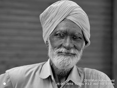 2018-10b Sikhism in Amritsar (51bw) (Matt Hahnewald) Tags: matthahnewaldphotography facingtheworld people character head face expression lookingcamera fullbeard dastar turban consent respect concept humanity living culture tradition religion religious traditional cultural gurdwara devotee worshiper pilgrim sikh sikhism goldentemple amritsar punjab india indian punjabi individual oneperson old man detail physiognomy nikond610 nikkorafs85mmf18g 85mm 4x3ratio resized 1200x900pixels horizontal street portrait closeup headshot seveneighthsview mono blackandwhite monochrome greyscale postprocessing editing posing positive eyebrows clarity quality