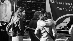 Street Browsing 01 (byronv2) Tags: street candid peoplewatching edinburgh edimbourg scotland blackandwhite blackwhite bw monochrome oldtown royalmile woman man shop stall market streetmarket marketstall jewelry jewelrystall kiosk browsing shopping celticjewelry