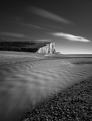 White Light (Explored) (Lloyd Austin) Tags: motion white light black grey exposure exposed february cuckmerehaven river cuckmere bw bnw blackwhite mono monochrome eastsussex england seascape sea seaside vista view landscape beach sand water pebbles rocks cliffs chalk sevensisters seafront walking sky longexposure lowtide slow cloudscape stacking filters 3lt cablerelease ethereal tranquility sigma1750mm d7200 dramatic serene nikon nature nationaltrust nationalpark gb