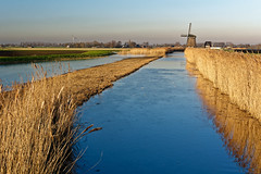 The Freezing Waters (Alfred Grupstra) Tags: nature water river windmill landscape ruralscene sky netherlands agriculture blue outdoors dyke farm lake field windturbine europe scenics 953 ice winter
