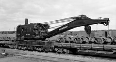 New Haven Railroad Maybrook Hook, a 150 ton capacity steam derrick # D-6, along with a couple truck cars, is seen in the yard at Maybrook, New York, ca 1940's (alcomike43) Tags: newhavenrailroad newyorknewhavenhartfordrailroadcompany maybrooknewyork railroadyard railroadderrick d6 150tonderrick crane outriggers boom pilleys cables truckcar flatcars trucks tracks mow maintenanceofway wrecker maybrookhook dieselized steam smoke steamderrick rails ties siding ballast roadbed jointedsectionrail rightofway freightcars boxcars hoppers hump photo photograph negative bw blackandwhite old historic vintage classic archbartrucks