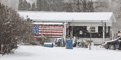 Patriotic Porch (wyojones) Tags: montana stignatius clouds snow winter trees feburary trailer house porch flag usflag painting car barrels snowing