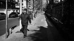 Morning exercices (Go-tea 郭天) Tags: qingdao shandong républiquepopulairedechine cn man old portrait exercices walk walking sport energy power powerful movement move sidewalk cold winter sun sunny shadow cap glasses alone lonely street urban city outside outdoor people candid bw bnw black white blackwhite blackandwhite monochrome naturallight natural light asia asian china chinese canon eos 100d 24mm prime