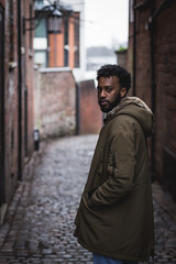 Alrasheed 2 (Qais Nidhal) Tags: portrait person alley brickwall face faded shallow united kingdom uk coventry street pathway old buildings lamp walk walking sudan africa black dark skin cold winter coat afro curly serious hope canon 50mm 600d 14