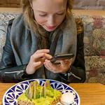 Food Bloggerin fotografiert ihr Avo-Toast aus Vollkorn mit Avocado, Yuzu Soße, Acai Soße, Pistazien und pochiertem Ei im Flax&Kale in Barcelona, Spanien thumbnail