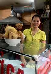 Vietnamese Chicken Girl (cowyeow) Tags: hanoi vietnam asia asian street urban city people girl young woman pretty yellow cute smile asiangirl vietnamese vietnamesegirl vietnamesewoman portrait restaurant food chicken dead funny composition vietnamesefood