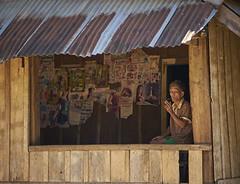 Khamu tribesman..zoom in on the pictures behind! (Tom Helleboe) Tags: luangsaycruises khamutribe mekong laos