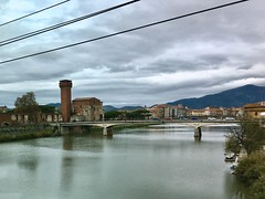 View from the train, Pisa (m4rguerite) Tags: pisa italy italia tuscany trainview bridge river fiume arno arnoriver fiumearno mutedcolors autumn cloudy cloudyday cloudysky clouds sky powerline powerlines tower cars traffic