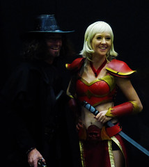 The Shadowman and the Lady in Red (Steve Taylor (Photography)) Tags: gun pistol blonde man woman lady newzealand nz southisland canterbury christchurch shadow armageddonexpo braidedhair costume ribbon v vendetta addington armaggedon hat outfit