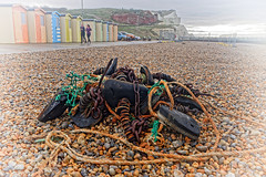 Flotsam (Croydon Clicker) Tags: flotsam jetsam debris rubbish net float rope twine chain rust beach shingle pebbles beachhuts runners people vignette sky cliff seaford eastsussex sussex