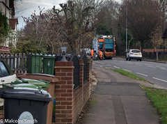Collection Day (M C Smith) Tags: refuse recycling collection working pentax k3 bins green brown gardens white black parking car cars overtaking letters numbers blue trees walls fence houses symbols emptying pavement kerb road orange hivi sky