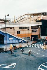 outside ueno station. (barbs--) Tags: cyclists cycling urban city urbangeometry bikes biking tokyo leicam6 kodakektar100 voigtländernokton35mm streetphotography lightandshadows transit intransit transportationhub uenostation