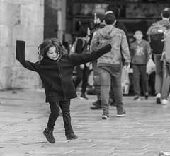 Who cares if I am poor, and wear a sweater that is twice my size? The Damascus gate's square is my playground and life is a game (ybiberman) Tags: israel jerusalem oldcity alquds muslimquarter damascusgate girl portrait candid streetphotography bw people jumping playing happy