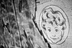 Ominously Serene (belleshaw) Tags: blackandwhite saltonsea streetart brickwall mural face boy circle paint tag name letters texture surface rough detail abstract