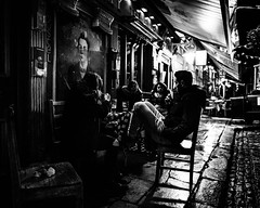 Night watcher (Kieron Ellis) Tags: man woman women bar outside drinking stools table painting eyes rainy wet cobblestones night dark smoking beer candid street blackandwhite blackwhite