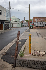 collingwood-2090-ps-w (pw-pix) Tags: poles bollards corner bent leaning damaged broken decayed gutter kerb asphalt bitumen concrete grafitti footpath road street grate grille drain rust rusted rusty corroded dilapidated weathered buildings houses warehouses homes commercial wet rain damp clouds cloudy warm hot humid summer signs fences laneway wires powerpoles tower clocktower townhalltower collingwoodtownhalltower trees treetops weeds cracked cracks rubble watermeter tap stopcock sinclairstreet dightstreet collingwood innersuburbs melbourne victoria australia peterwilliams pwpix wwwpwpixstudio pwpixstudio