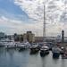 Ausblick von der Rambla de Mar Brücke auf Jachten und Luxusboote im Hafen Port Vell mit Turmuhr in Barcelona, Spanien