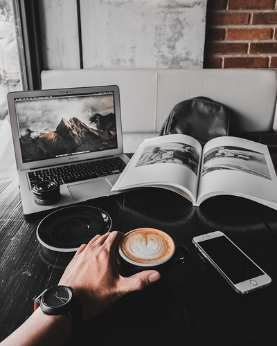 man holding cup of latte on table with MacBook Air and book - Credit to https://myfriendscoffee.com/