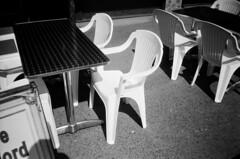 White plastic chair (Matthew Paul Argall) Tags: hanimex35es fixedfocus focusfree 35mmfilm kentmerepan100 100isofilm blackandwhite blackandwhitefilm chair chairs table