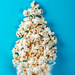 Flat lay of popcorn cup on a blue background. Top view thumbnail