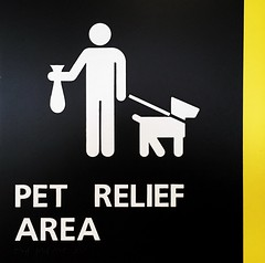 Pet Relief Area Sign | Portland International Jetport Portland, Maine (steveartist) Tags: signs informationalsigns airportsigns portlandme petreliefareasign symbols man dog poobag leash typereversedoutofblack verticalyellowarea