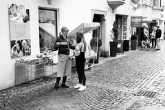 Street life in Brixen (auqanaj) Tags: 02201920190309 kodakgold200 olympus35rc analog cewescanat72dpi film brixen bressanone italie südtirol southtyrol altoadige cobblestone street strase strasenszene bedienung waitress friendly monochrome schwarzweis blackandwhite