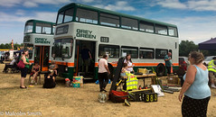 Bus Rally (M C Smith) Tags: blue green grey bus buses sales woman women man men tables grass numbers letters symbols rally chairs clouds red flag hivi wheelchair parking cars stalls silver orange yellow sitting bags boxes trees
