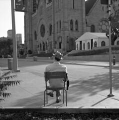 untitled (kaumpphoto) Tags: rolleiflex 120 tlr ilford black white city urban street portrait view one chair man minneapolis nicollet church wait sit hat single road