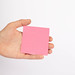 Hand holding empty pink paper isolated on white background