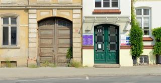 1-9896   Alt und neu in der Eisenbahnstraße von Güstrow;  restauriertes Gebäude mit frisch lackierte Holztür und Glasfenstern neben einem verlassenen Gebäude dessen Toreinfahrt mit einem alten Tor verschlossen ist.