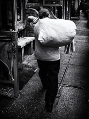 Bag Handler (Feldore) Tags: newyork chinatown street candid man carrying bag sack walking feldore mchugh em1 olympus 17mm 18