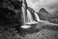 Kirkjufellsfoss in Monochrome (azhukau) Tags: iceland nature waterfall landscape water scenics mountain outdoors rockobject beautyinnature grass famousplace river greencolor travel sky nordiccountries moss stream summer kirkjufell kirkjufellsfoss tourist attraction blackandwhite monochrome longexposure