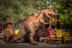 Rex looks like he is about to have a Coke. (donnieking1811) Tags: arizona sedona guillermogardens tyrannosaurusrex tyrannosaurus signs coke cocacola furniture outdoors trees hdr canon 60d lightroom photomatixpro
