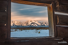 Through the Window (kevin-palmer) Tags: december winter cold snow snowy nikond750 tamron2470mmf28 moran grandtetonnationalpark tetons mountains cunninghamcabin old historic structure logcabin building window morning sunrise dawn cloudy overcast color colorful orange